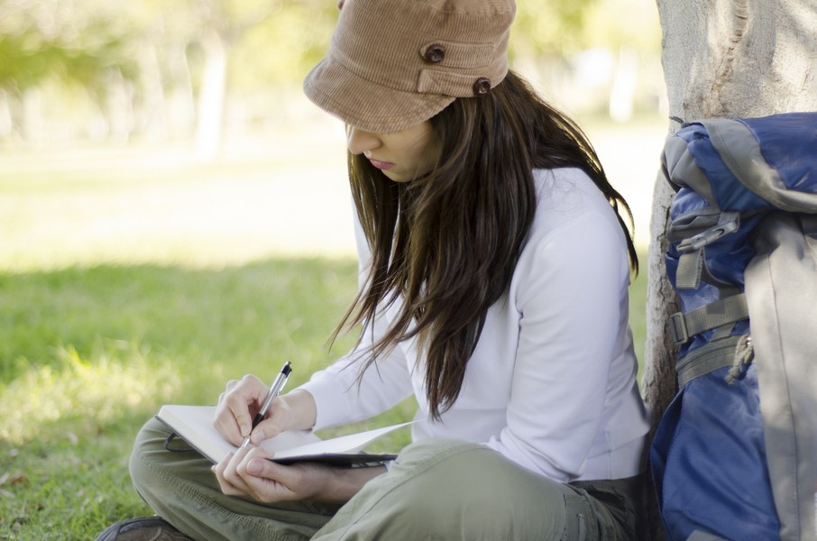 Young beautiful woman writing on a journal about her hiking trip